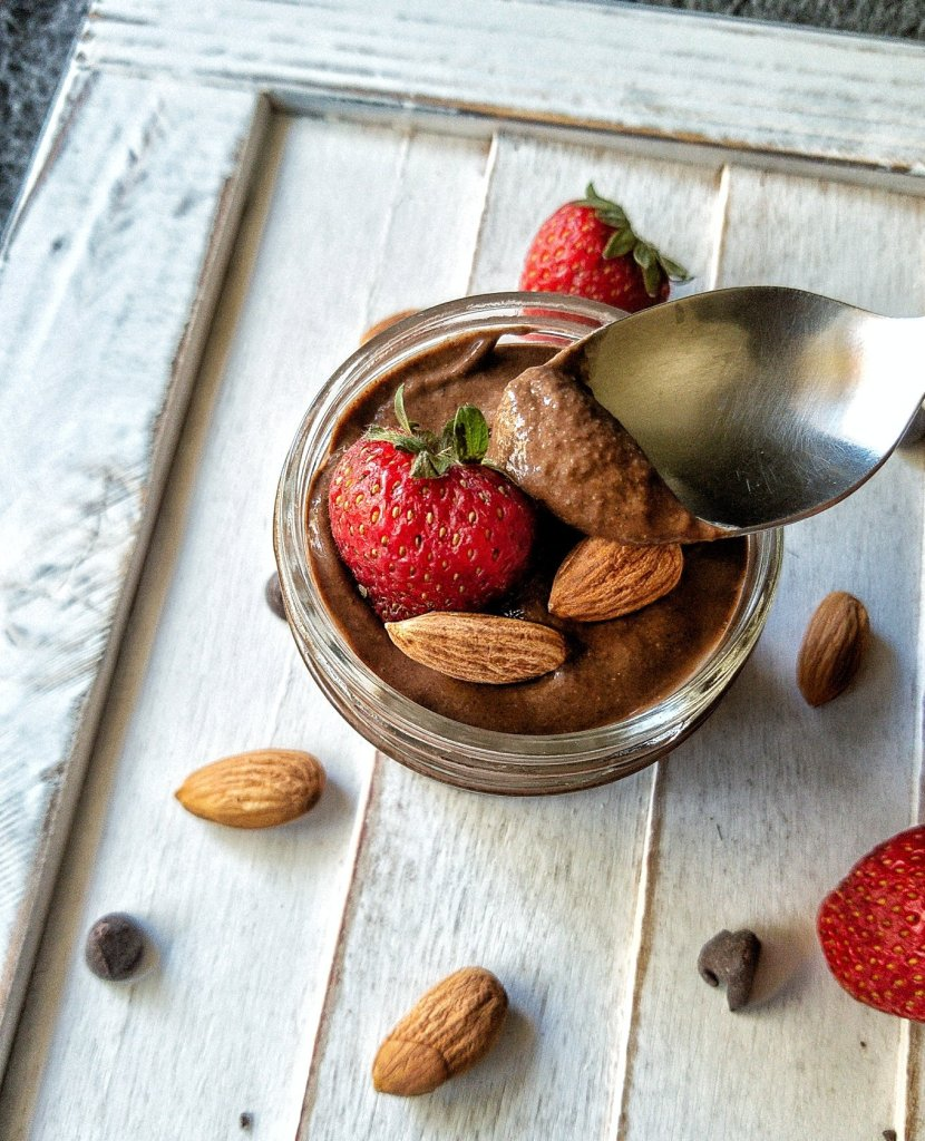 Chocolate chia seed pudding in a small, single-serving jar topped with strawberries and almonds.