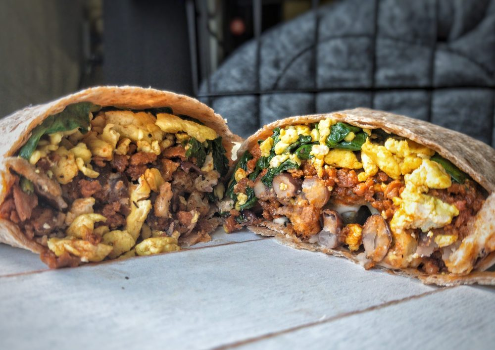 Wrapped burrito cut in half with beans, soyrizo, tofu scramble, and potatoes inside