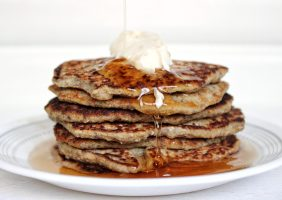 Stack of gluten-free banana vegan pancakes with vegan butter and syrup