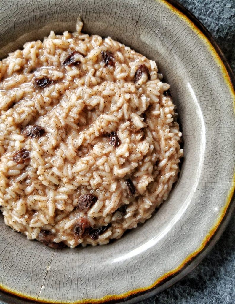 Bowl of rice pudding with pantry raisins and cinnamon.
