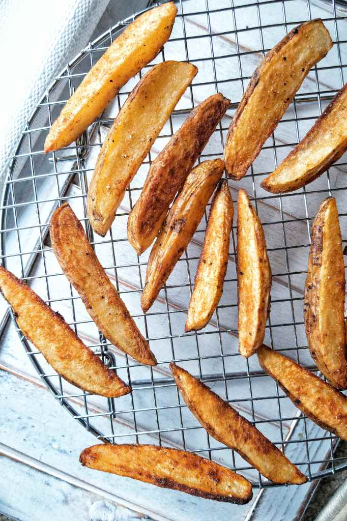 Crispy potato wedges snack baked in the oven and seasoned with salt on a metal, cooling rack