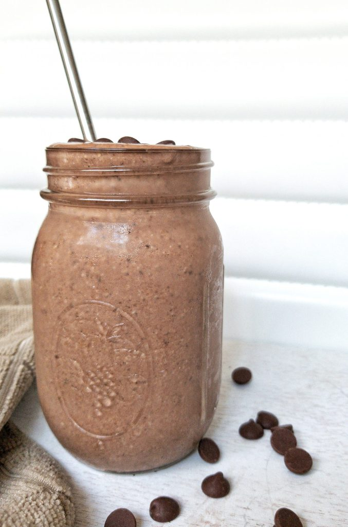 Chocolate peanut butter smoothie in a glass mason jar topped with chocolate chips