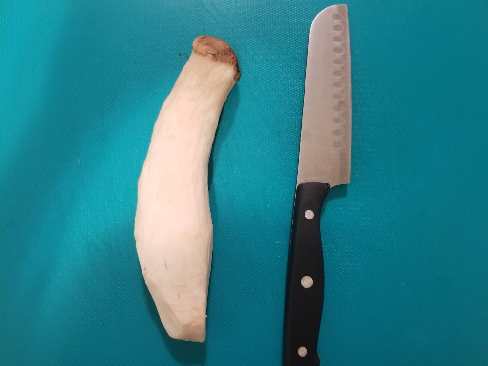 One whole king oyster mushroom with a knife