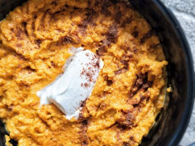 Mashed carrots in a black bowl topped with more ground cinnamon and butter