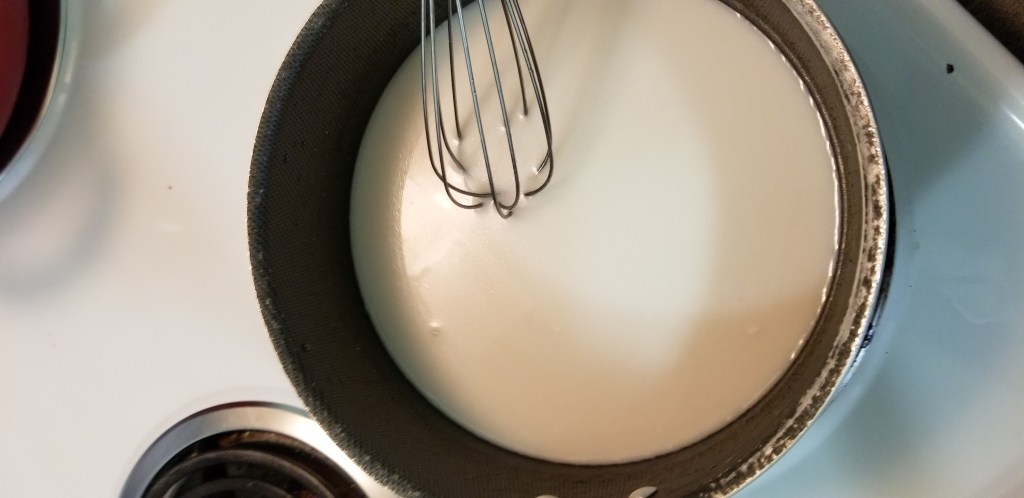 Saucepan with coconut milk and sugar and a whisk
