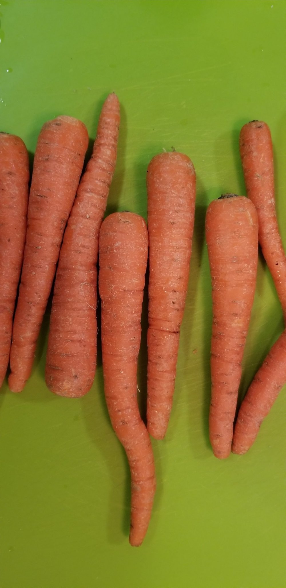 Whole carrots on a green chopping board