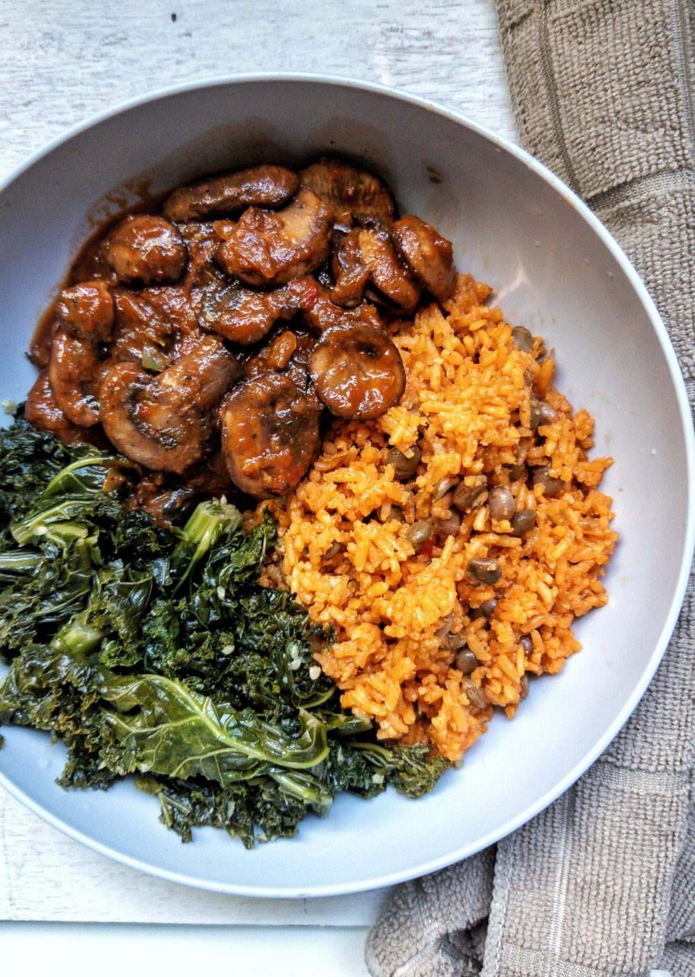 Puerto Rican yellow rice with a side of stewed mushrooms and braised kale in a gray bowl