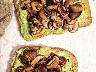 Two slices of toasted bread topped with smashed avocado and mushrooms