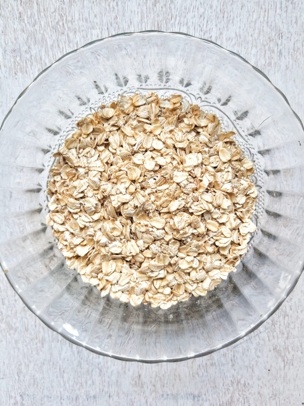 Rolled oats or old-fashioned oats in a clear, glass bowl.