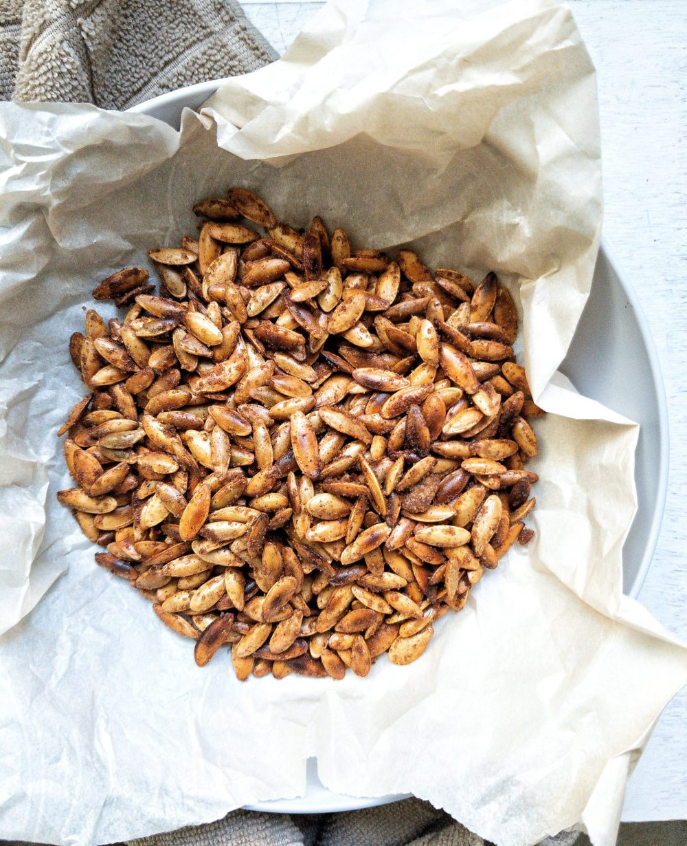 Toasted cinnamon brown sugar pumpkin seeds in a bowl lined with parchment paper