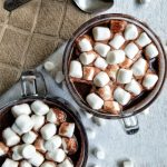 Two cups of hot chocolate topped with marshmallows