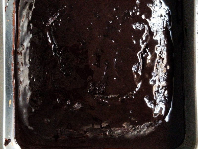 Baked vegan chocolate Devil's Food Cake in a small baking cake pan with a chocolate glaze