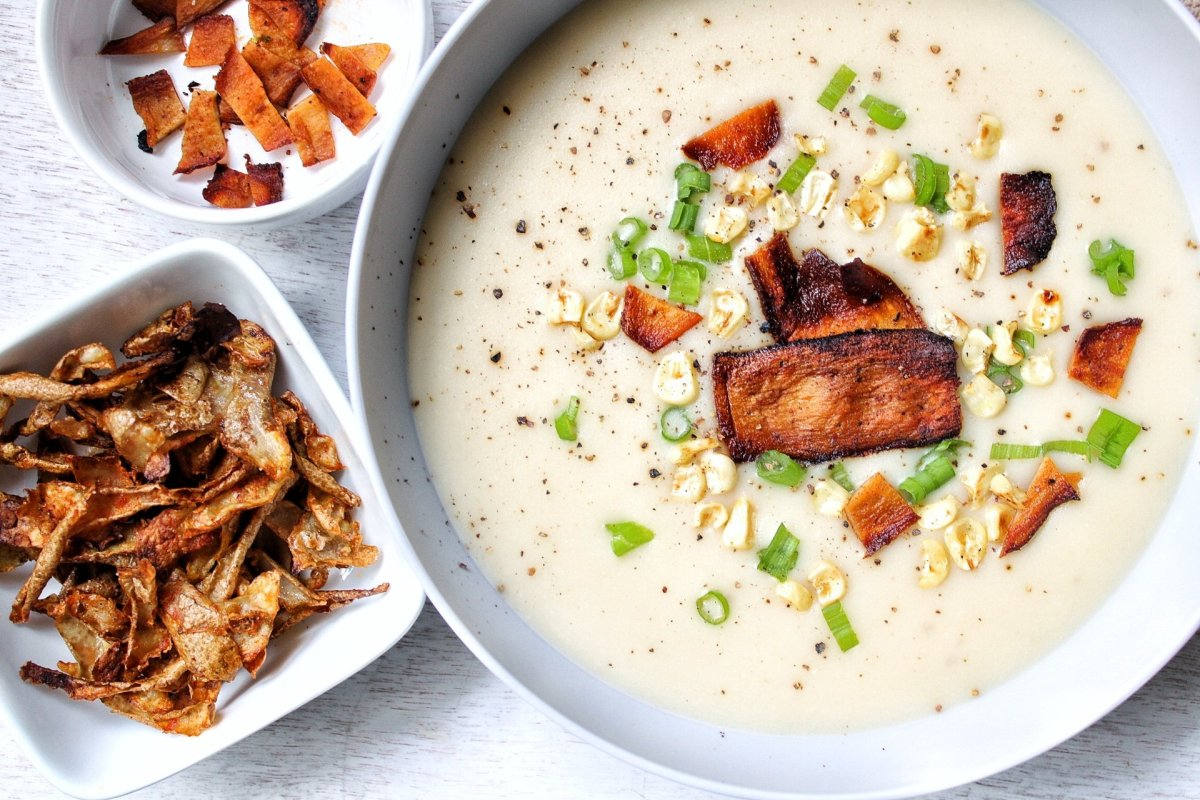 Plant-based creamy, garlic potato soup topped with vegan bacon, green onions, and corn. With a side of roasted potato peels.