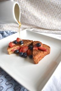 Stuffed french toast topped with fruit and syrup