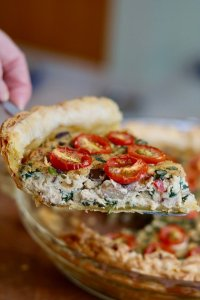 Slice of vegan quiche with mushrooms and spinach