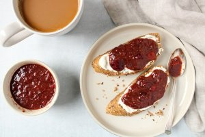 There are 2 slices of bread on a plate topped with vegan cream cheese and homemade cherry marmalade. On the side, there is a pale hand towel, a cup of coffee and a small bowl with more of the fruit spread.