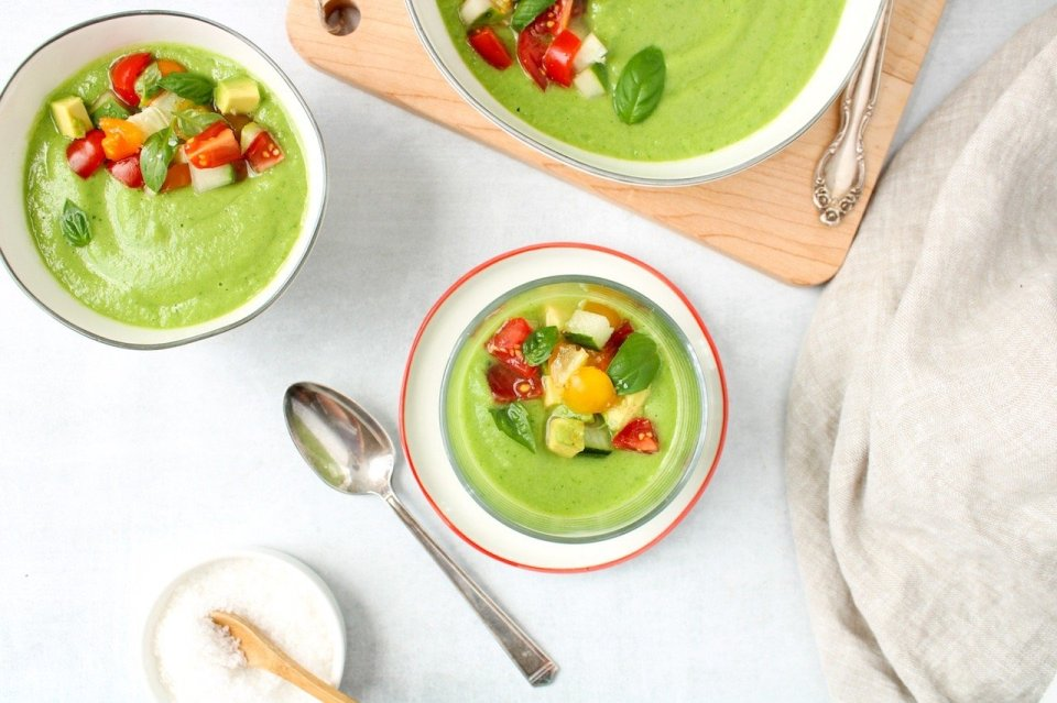 Over head shot on a vegan cold cucumber soup that is topped with tomatoes, avocado, cucumber and basil. There is a spoon on the side and you can see a portion of 2 other bowl containing some of the soup.
