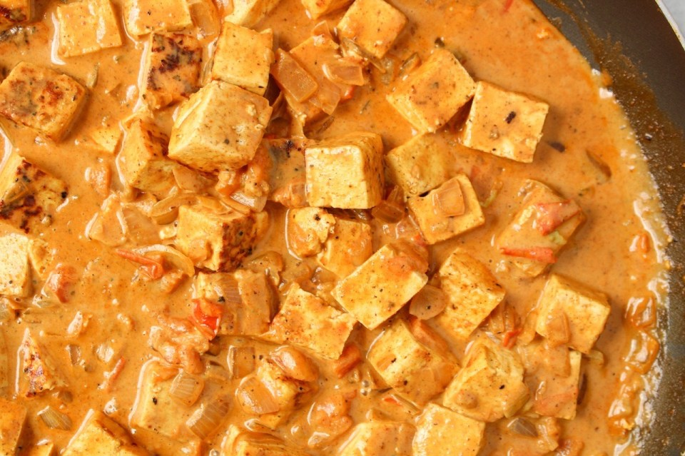 Cubes of tofu in a pan mixed with a creamy red-pink sauce and small pieces of onions and tomatoes