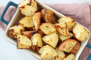 Quartered roasted red potatoes piled in a white serving dish