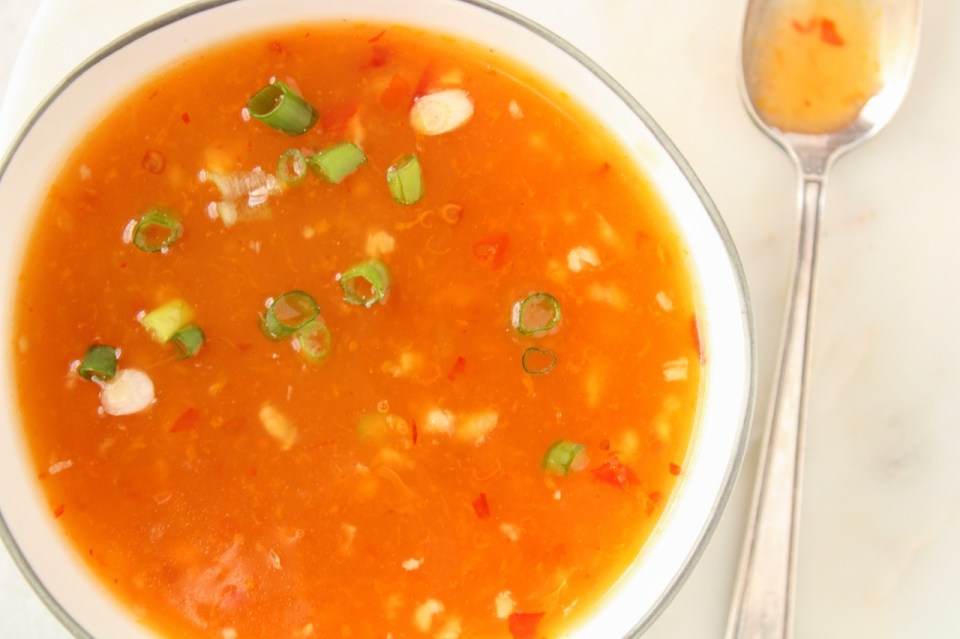 In a white bowl, you can see a close up of a sweet and spicy orange sauce. On the side, there is a spoon covered with the sauce.
