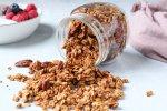 A glass jar containing some sweet potato granola is tilted on the side on the table and you can see the granola falling out. On the side and in the background, there are a yogourt breakfast bowl topped with granola and also a pink hand towel.