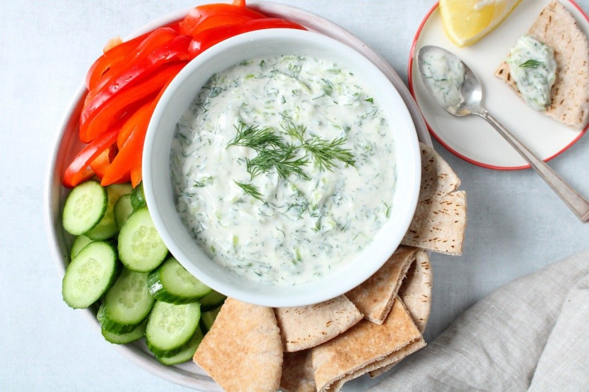 Homemade Vegan Tzatziki is displayed in a white bowl. The bowl is on a plate and surrounded by sliced cucumber, red pepper and pita bread. On the side on the table, there are 2 lemon wedges and a hand towel.