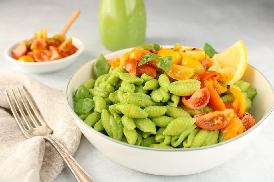 There is white bowl containing noodles covered in a creamy green sauce and topped with sliced cherry tomatoes. Also in the bowl on the side, there is a slice of lemon and fresh basil leaves. On the table, there is a small bowl with sliced tomatoes.