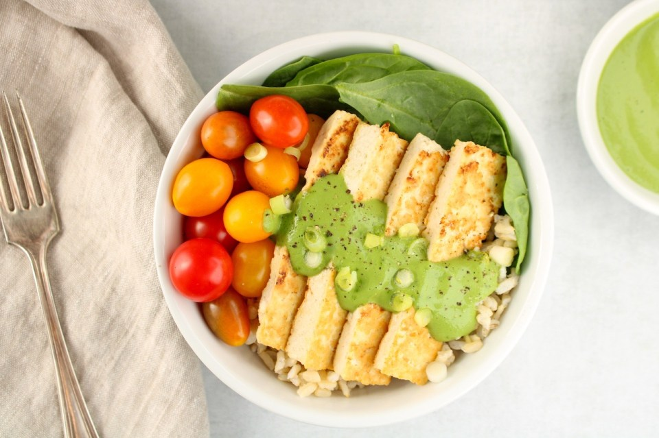 Displayed in a white bowl: fresh spinach, brown rice, roasted tofu and cherry tomatoes topped with a creamy green sauce and green onion.
