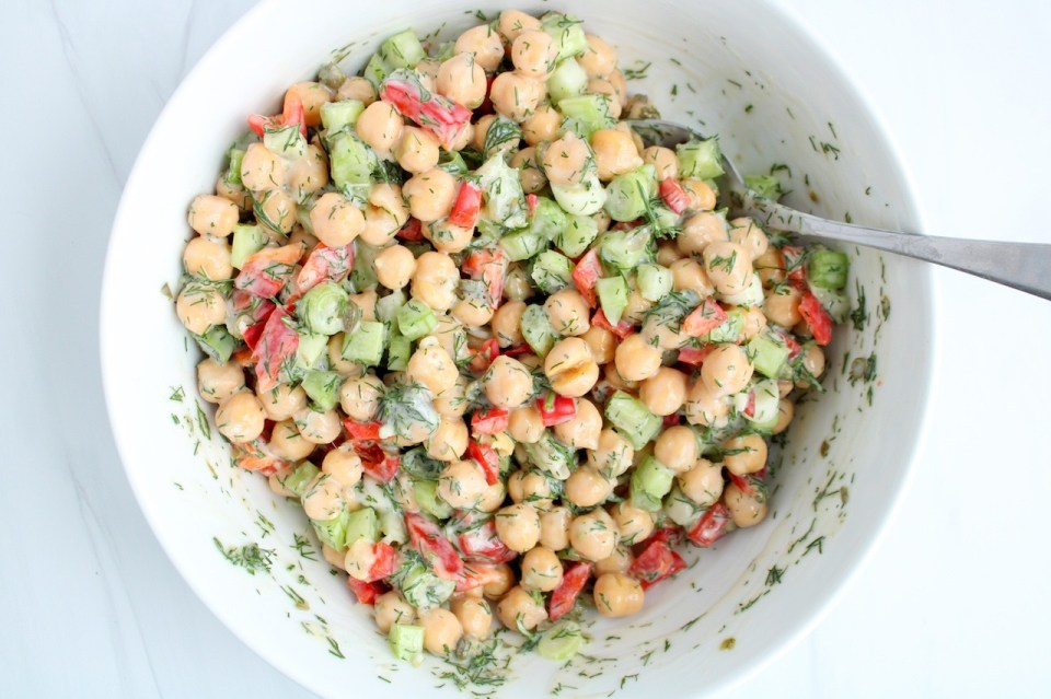 In a large white bowl, there is a dill chickpea salad with a large spoon stirring the ingredients together.
