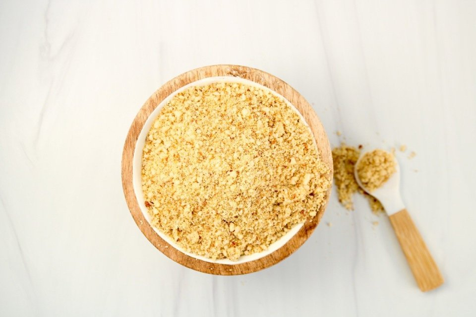 In a small wooden bowl, you can see a dairy-free parmesan cheese made with almonds. Also on the side of the bowl, there is a small white spoon on the table with some of the almond parmesan cheese falling off.