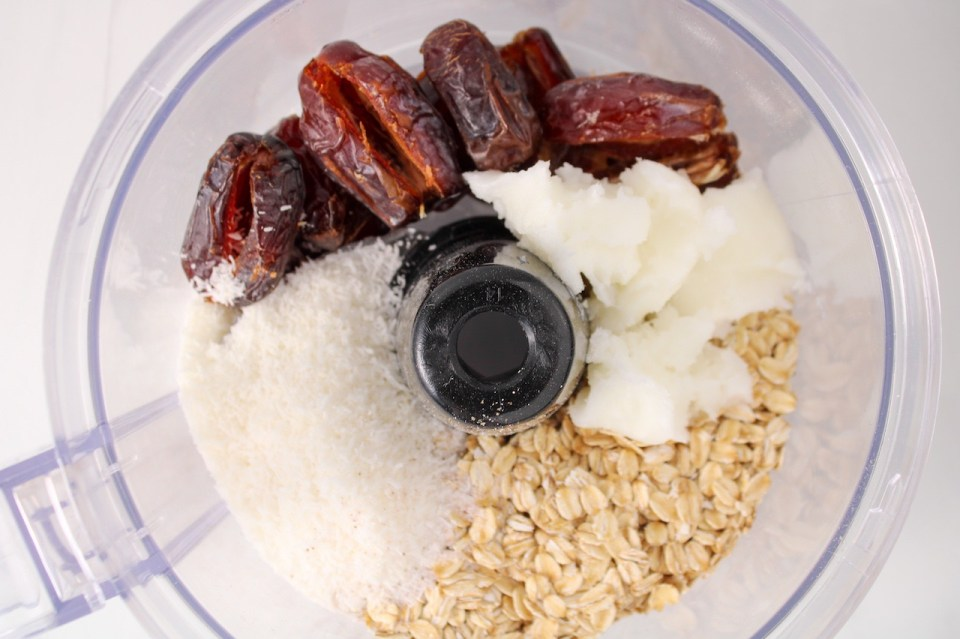 Showing is the inside of a food processor containing dates, raw oats, coconut oil and shredded coconut