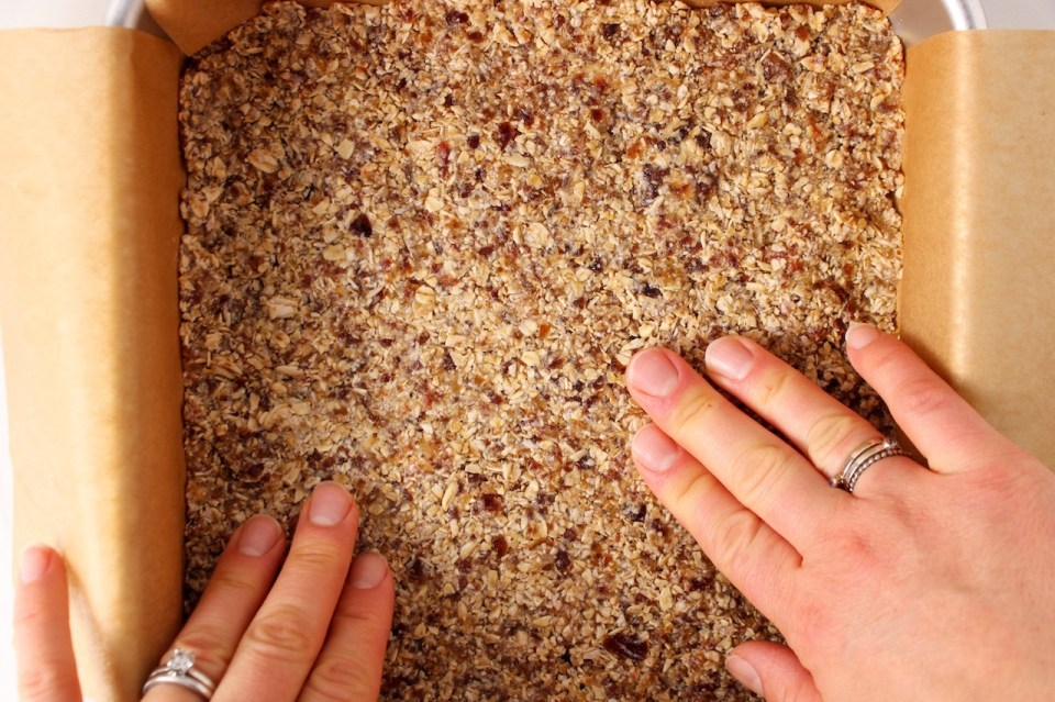 You can see 2 hands pressing on a date and oat mixture.