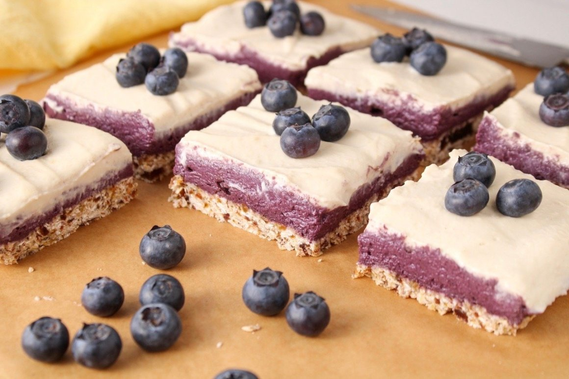 Close up on a few squares of vegan blueberry cheesecake displayed on a piece of parchment paper. There is a yellow hand towel in the background.