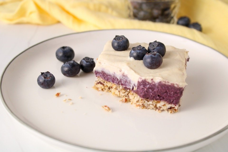 Displayed is a piece of vegan blueberry cheesecake in a square shape and topped with fresh blueberries. The piece is placed on a white plate with more blueberries around.