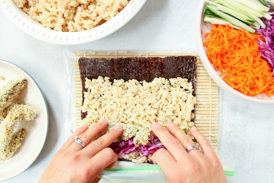 Some brown rice has been layered on a nori sheet, also with a few garnishes. Also on the side: a large bowl of brown rice, an other bowl of cut veggies (carrots, cucumber, purple cabbage) and one more bowl containing avocado tempura.