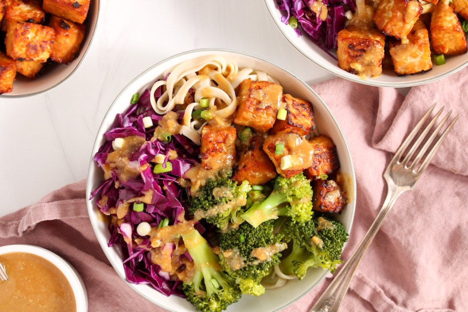 Showing is 2 white bowl (one you can only see half of it) containing brown rice noodles that are topped with miso tempeh, shredded red cabbage and steamed broccoli. There is a drizzle of a miso sauce on top as well as sliced green onion. On the table on the side, there is a pink hand towel, a fork, a small white bowl with more of the tempeh and a bowl with a miso sauce.