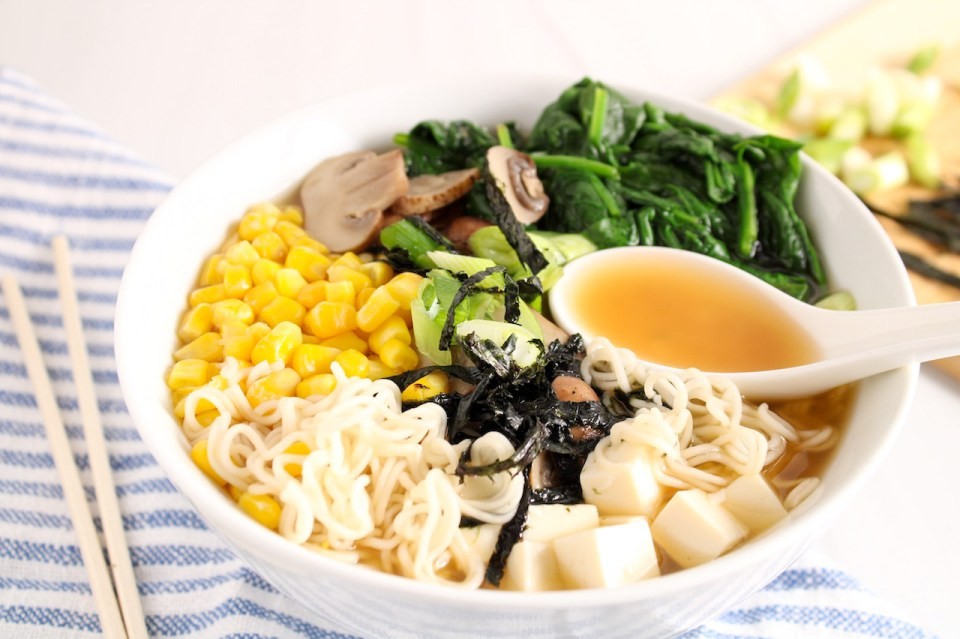 Showing is a miso ramen soup in a large white bowl that is topped with corn, wilted spinach, green onion, silken tofu and nori seaweed. You can see some of the ramen noodle floating beside all of the toppings as well as a few pieces of sliced mushrooms. There is also a white Asian style spoon on top on the noodle hanging on top. On the table on the side, there is a lined white an blue hand towel, a pair of chop sticks and a wooden cutting board with green onions and more nori seaweed.
