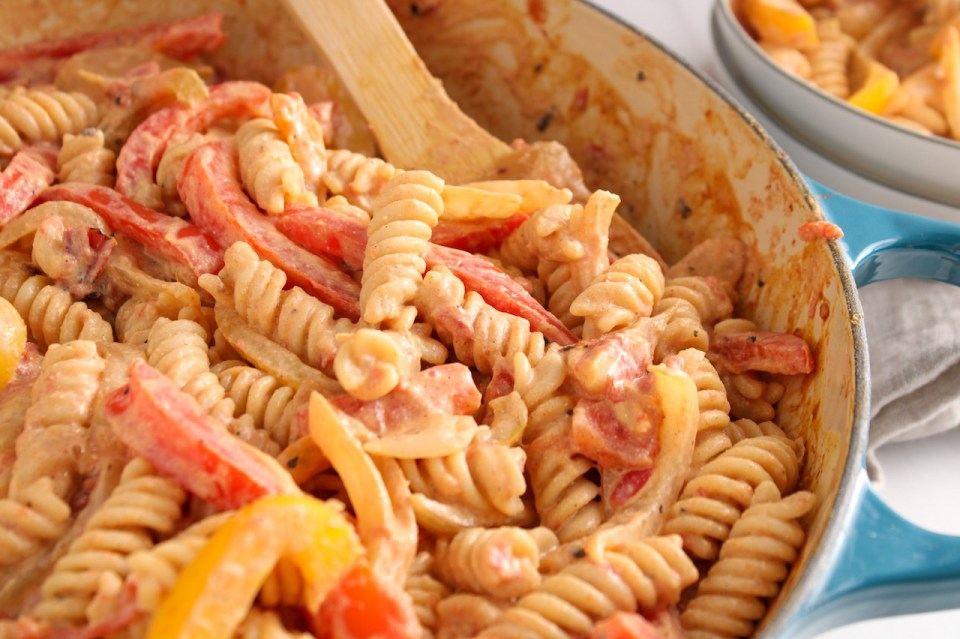 Close up inside a pan showing rotini noodles with sliced onion and peppers in a creamy tomato sauce.