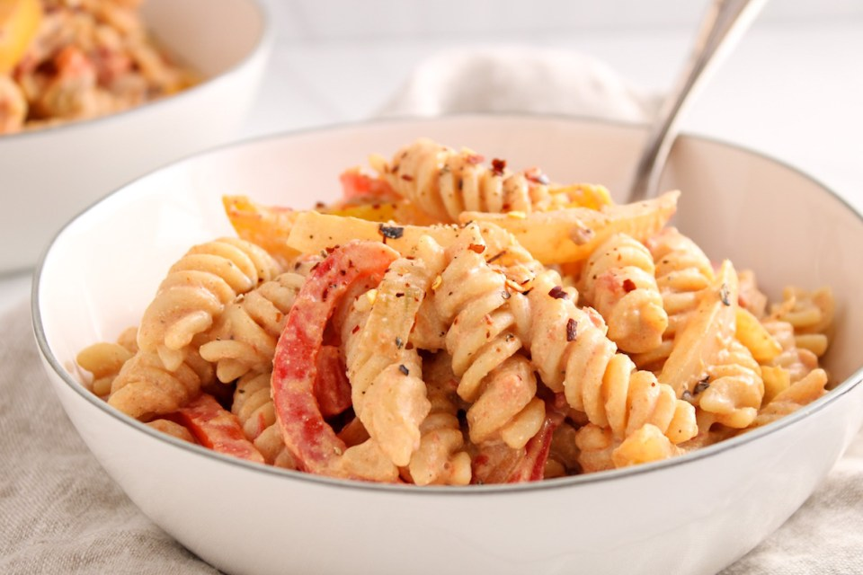 Close up on a vegan creamy pasta dish with sliced peppers and onion and with a sprinkle of red pepper and black pepper.