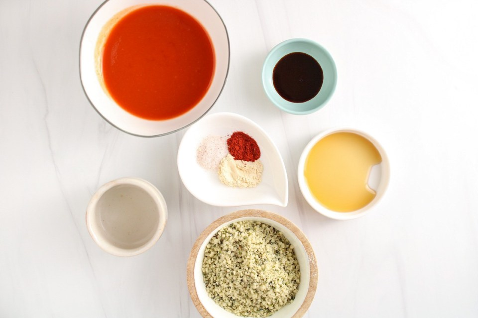 Ingredients needed to make a homemade vegan buffalo sauce, displayed are cayenne pepper hot sauce, white vinegar, salt, garlic powder, smoked paprika, maple syrup, hemp seeds and Worcestershire sauce.