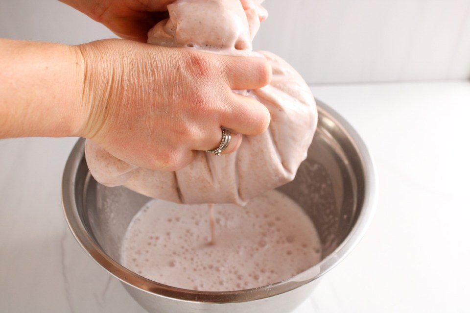 There are 2 hands pressing on a nut milk bag to strain nut milk