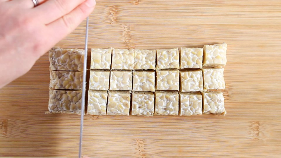 Showing is tempeh being cut in cubes, you can can a knife and a hand in the action of cutting.