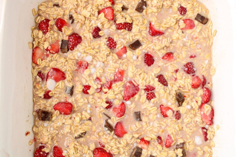There is a mixture of raw oats, vegan milk, strawberries and chocolate in a baking dish.