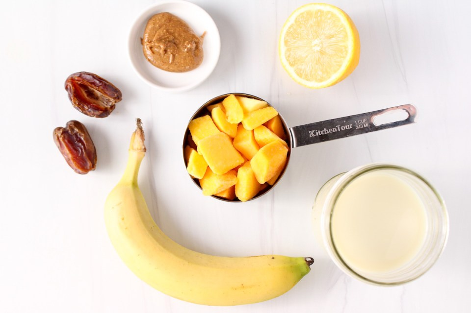 Showing are the ingredients to make a frozen fruit drink. There are mango chunks, dates, a banana, almond butter, oat milk and half of a lemon.
