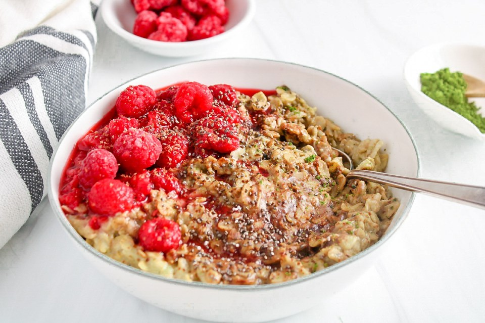 Showing is a white bowl containing a creamy matcha oatmeal topped with raspberries and chia seeds with a spoon on the side of the bowl. On the side, there is more raspberries in a small white bowl, matcha powder in a small white bowl and a hand towel.