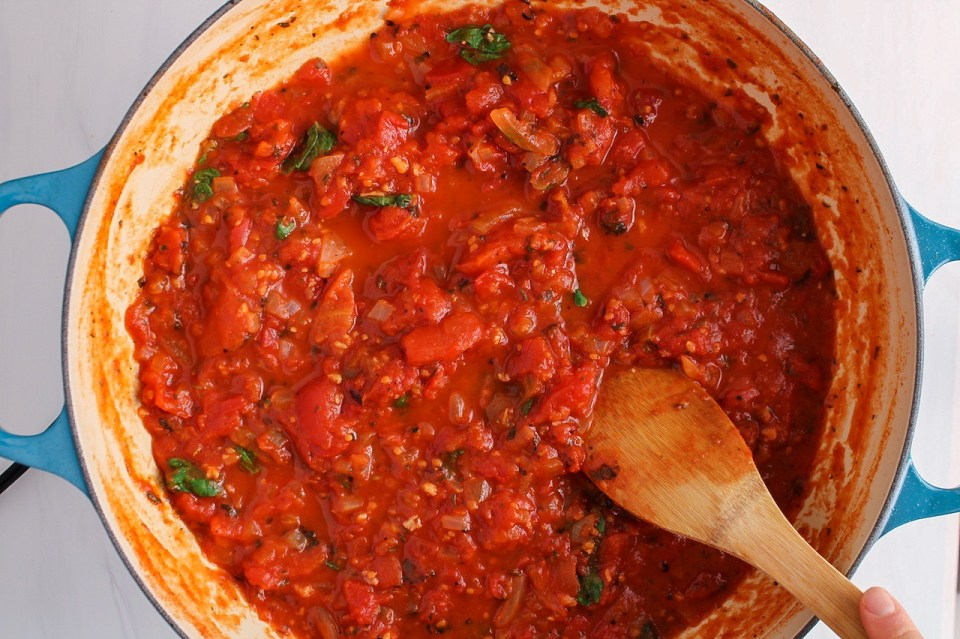 Tomato pasta sauce in a large pan with a hand stirring using a wooden spoon.