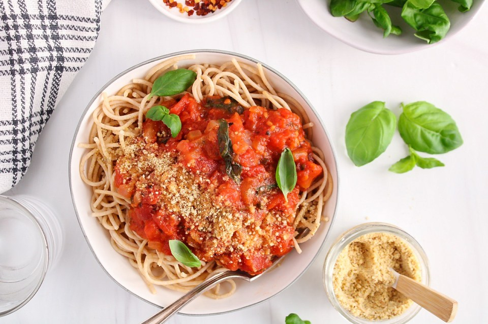 There is a white bowl with noodles topped with a hearty marinara sauce and fresh basil. There is some vegan parmesan cheese in a jar on the side, as well as a black and white hand towel, red pepper flakes and a glass of water.