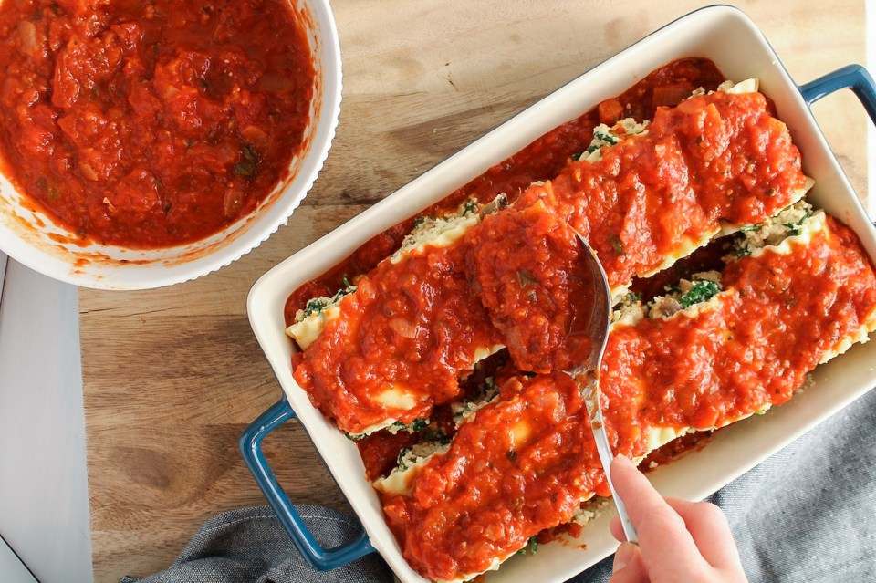 There is a hand spreading some marinara sauce over noodles in a baking dish that were stuffed with a creamy filling.
