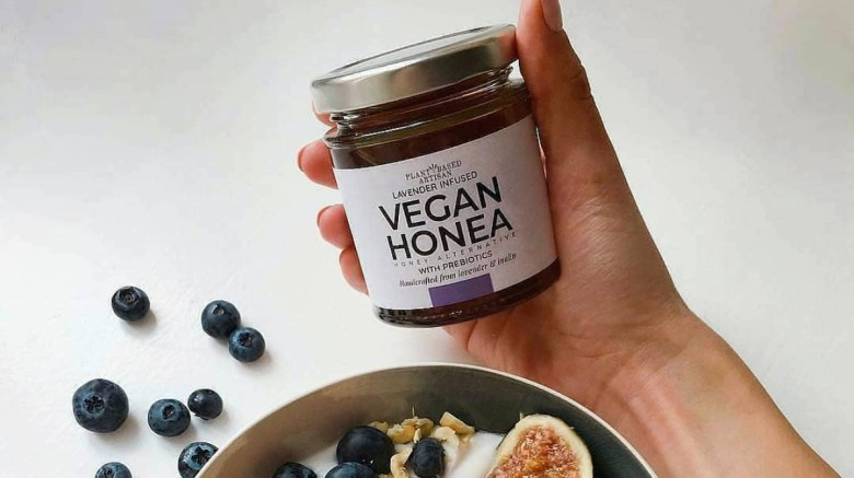 A hand is holding a jar of Plant Based Artisan Vegan Honea, above a bowl of blueberries