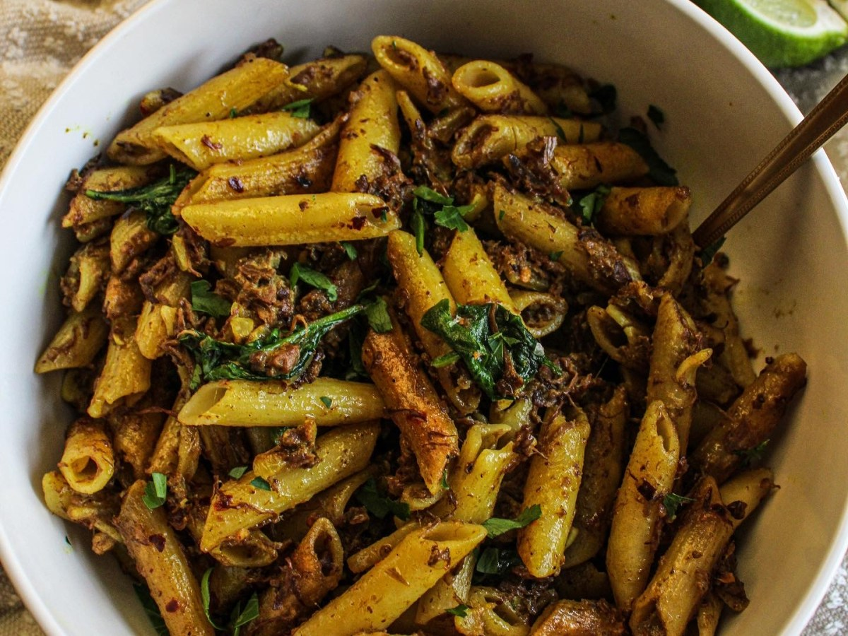 Curried jackfruit penne pasta in a bowl topped with cilantro and lime
